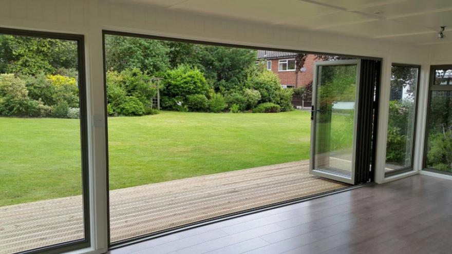 2 large full length aluminium windows sit each side of the matching bi-fold doors