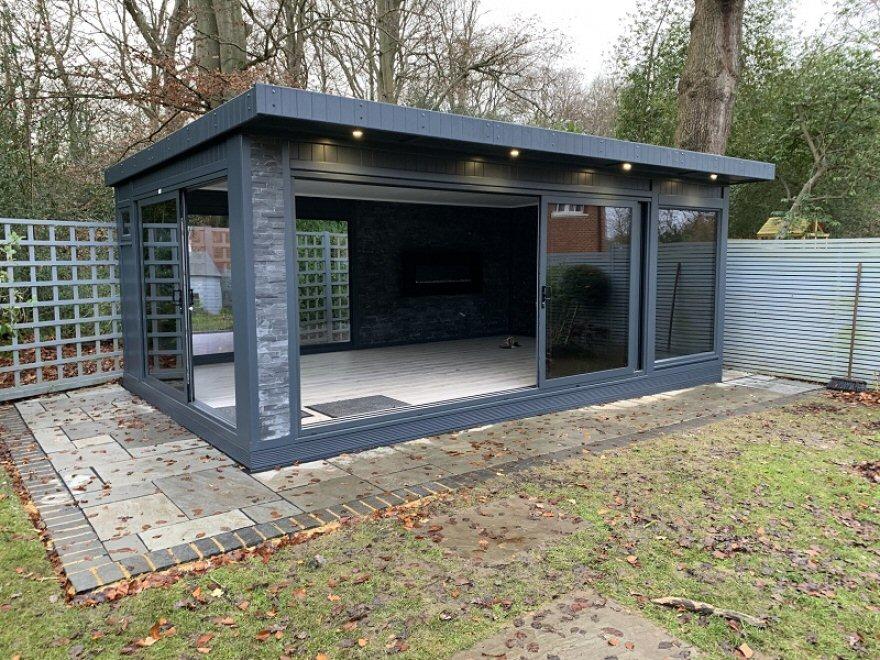 The office features aluminium tri-sliding doors with a slate stone external pillar in 'maxi black'