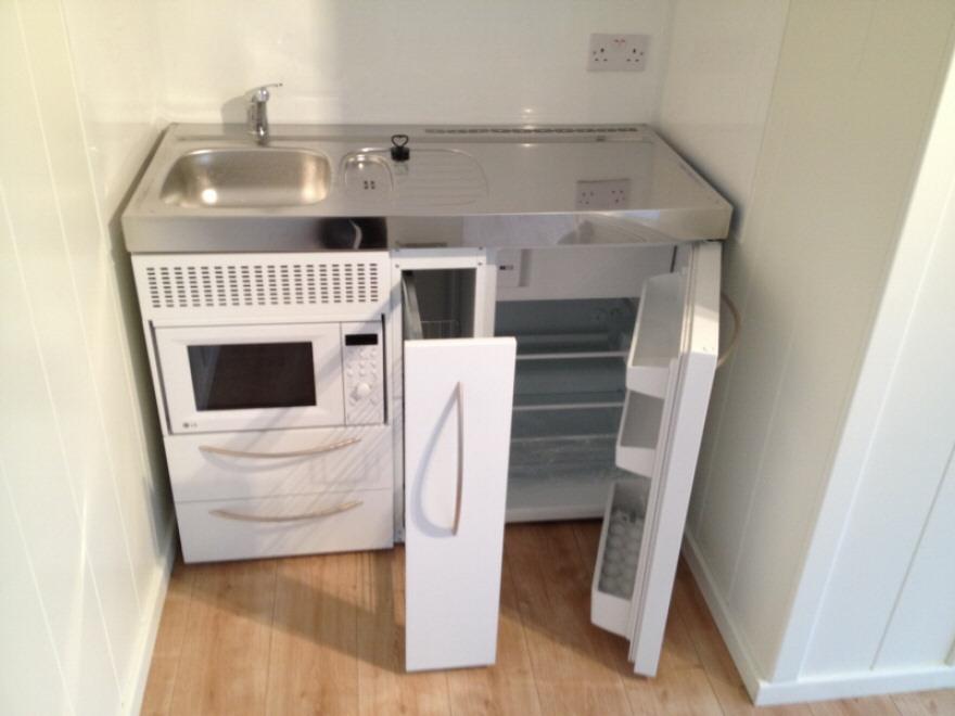 intergrated sink, micowave, fridge and storage next to toilet