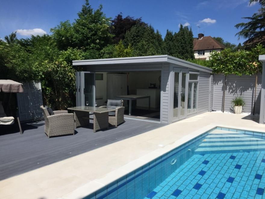 bifold door summerhouse beside garden swimming pool